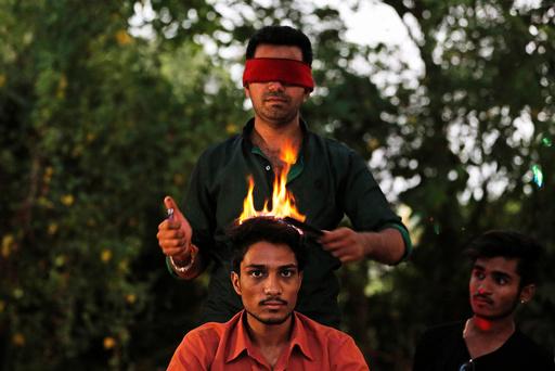 Vishnu Limbachiya, a hair artist, styles the hair of a man while wearing a blindfold at a park in Ahmedabad