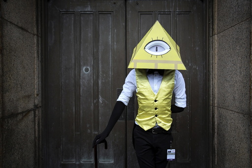 Louscher dressed as Bill Cipher from Gravity Falls poses as he attends Day Two of New York Comic Con in Manhattan