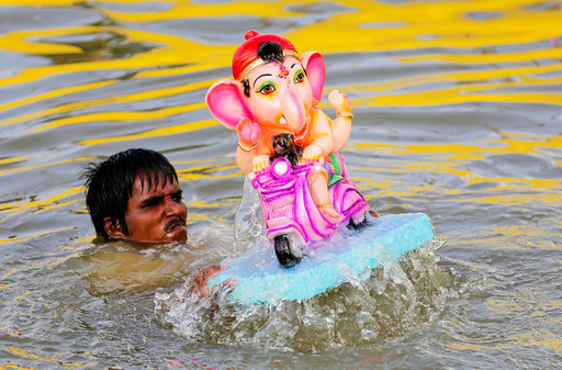 A man immerses an idol of Hindu god Ganesh, the deity of prosperity, in a pond on the second day of Ganesh Chaturthi festival in Ahmedabad