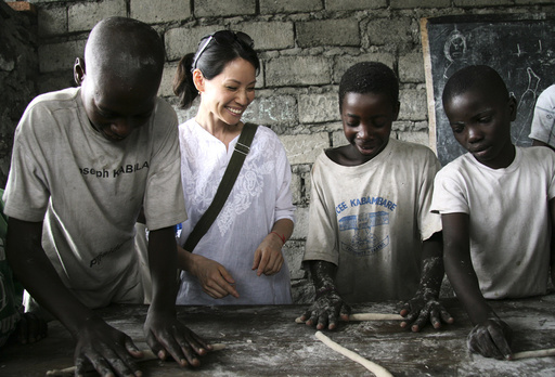 UNICEF Ambassador Lucy Liu kneads dough with boys at a reinsertion center in Goma