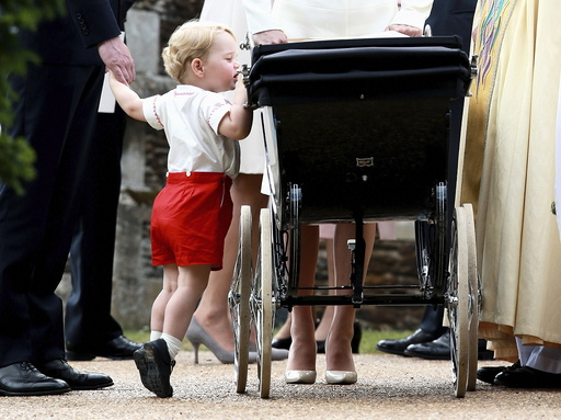 Britain's Prince George looks into the pram of his sister Princess Charlotte after her christening at the Church of St. Mary Magdalene in Sandringham