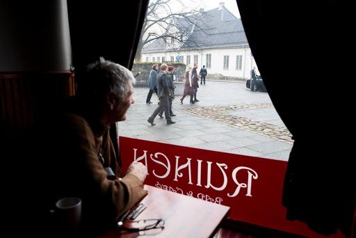 En cafegjest på Ruinen bar&cafe følger med når kronprins Haakon og kronprinsesse Mette-Marit besøker bydel Gamle Oslo tirsdag.