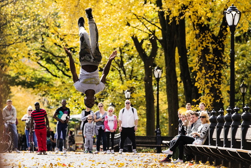 A street performer jumps in the air inside Central Park as the colors of autumn become more prevalent in New York