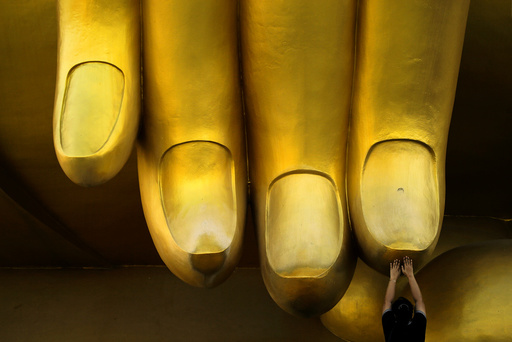 A woman prays while touching the fingers of a Buddha statue during the annual Makha Bucha Day, which celebrates Buddha's teachings, in Ang Thong
