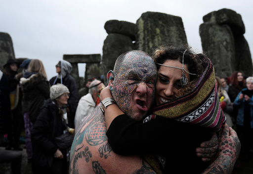Visitors and revellers react amongst the prehistoric stones of the Stonehenge monument at dawn on Winter Solstice, near Amesbury