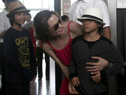 Hollywood actress Angelina Jolie chats with her adopted son Pax Thien at a security check point before leaving Con Dao island