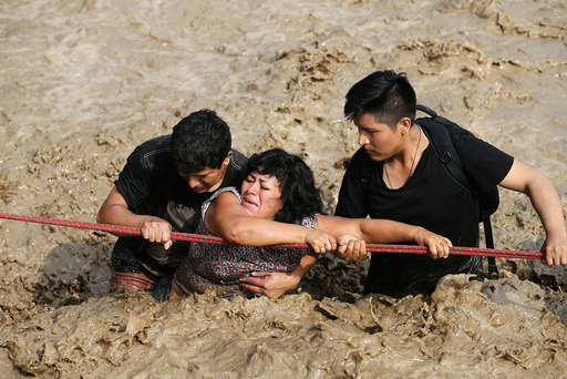 A woman is assisted while crossing a flooded street after the Huaycoloro river overflooded its banks sending torrents of mud and water rushing through the streets in Huachipa