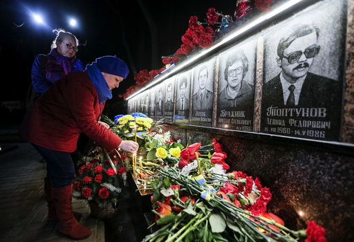 A woman lays flowers at a memorial, dedicated to firefighters and workers who died after the Chernobyl nuclear disaster, during a night service in the city of Slavutych
