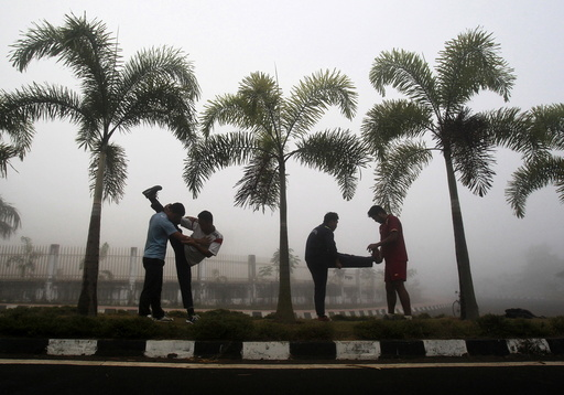 Men stretch during their routine exercises on a road divider during a foggy morning in Agartala
