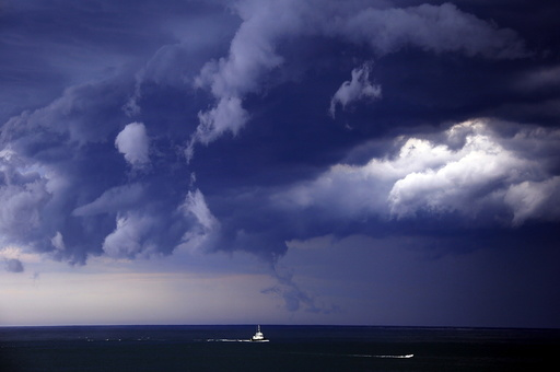Boats head into shore as storm clouds move along the coast towards the city of Sydney, Australia