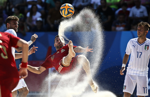 Gomez of Spain kicks the ball next to Marinai of Italy during their group stage beach soccer match at the 1st European Games in Baku