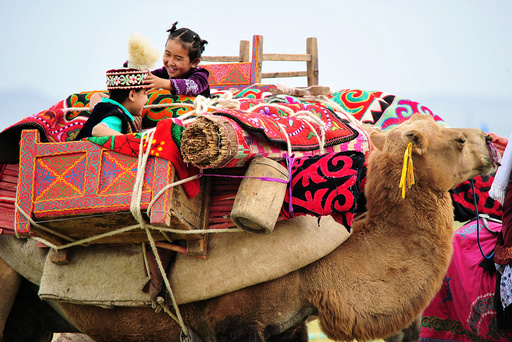 Children play on the camel during a traditional sports meeting in Barkol Kazakh Autonomous County
