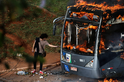 A man lights up his cigarette with the flames of a bus burned by anti-government demonstrators during a protest against the constitutional amendment PEC 55, which limits public spending, in front of Brazil's National Congress in Brasilia