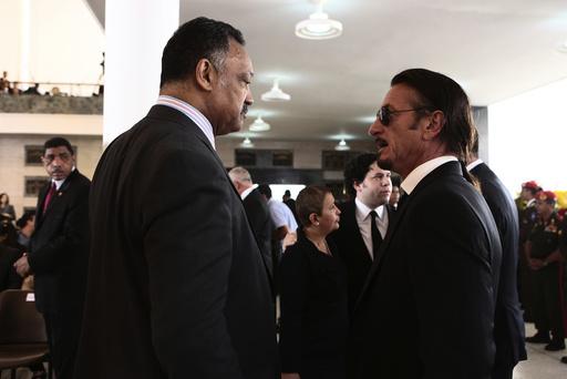 Civil rights leader Rev. Jesse Jackson Sr. talks with actor Sean Penn during the funeral for Venezuela's late President Hugo Chavez in Caracas