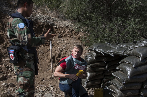 British actor Daniel Craig, a UN advocate against use of landmines and explosives, gets a briefing from Cambodian de-miners at an active minefield in Cyprus