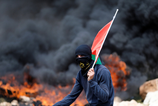 Protester holds a Palestinian flag as smoke rises from burning tyres during clashes with Israeli troops at a protest against Jewish settlements, in al-Mughayyir village near the West Bank city of Ramallah