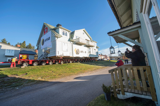 Neighbors take pictures of a house being moved in Malmberget