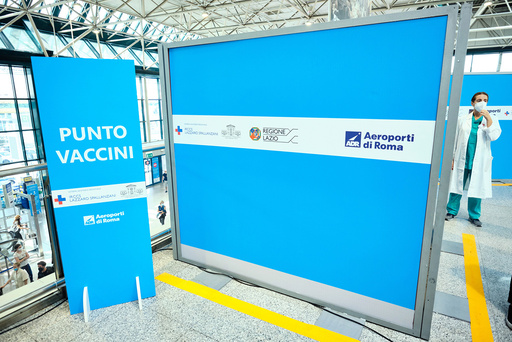 A doctor stands at a vaccination center, Vax & Go, set up at Rome's terminal 3 Leonardo da Vinci airport, where passengers can get a first or second vaccination dose by just showing their boarding card, in Fiumicino, Italy, Tuesday, July 27, 2021. With daily COVID-19 cases sharply rising again, Italy requires people to have received at least one vaccine dose, have recovered from the illness in the last six months or have proof of a negative test performed in the last 48 hours to access venues like gyms, museums and indoor restaurants in a bid to avoid a return to pandemic lockdowns devastating for the economy. (Mauro Scrobogna/LaPresse via AP)