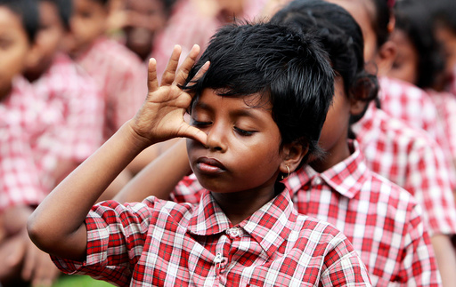School students practice yoga during a training session ahead of World Yoga Day in Agartala