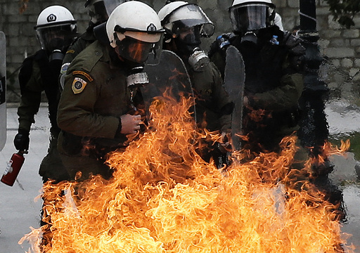 Riot police react to petrol bombs thrown by masked youths in Syntagma Square during a 24-hour general strike against planned pension reforms in Athens