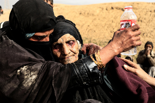 Displaced Iraqi women who just fled their home,rest in the desert as they wait to be transported while Iraqi forces battle with Islamic State militants in western Mosul