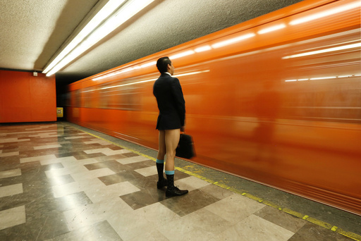 A passenger without pants waits for the subway train during