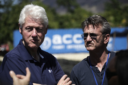Former U.S. President Clinton and actor Penn listen to explanations by cooperative members of a local for-profit farming cooperative supporting agricultural development, during a tour to the Lime nursery, on the outskirts of Mirebalais