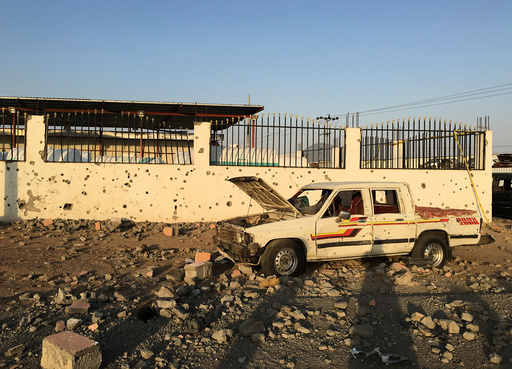 Car sits next to a salvage yard hit by a Houthi rocket in an industrial area in eastern Najran city