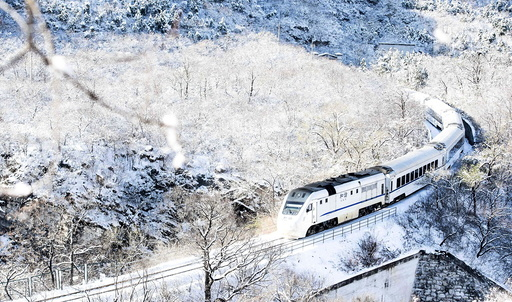 A train travels through hills covered by snow after heavy snowfall on the outskirts of Beijing