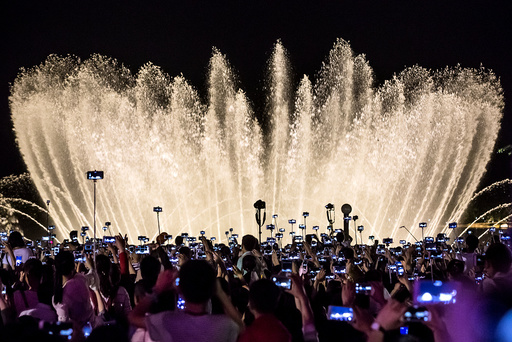 People record a water fountain show with their mobile phones in Hangzhou