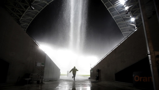 A man runs to protect himself from heavy rain as the French Ligue 1 soccer match between Nice and Nantes is stopped at Allianz Riviera stadium in Nice
