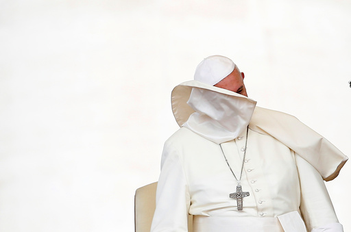 A gust of wind blows off Pope Francis' mantle during the weekly audience in Saint Peter's Square at the Vatican