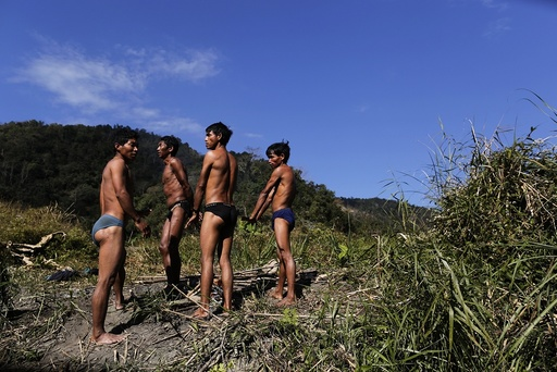 Naga men warm themselves by a fire after collecting fish in an icy creek near their hunting base camp in a opium field between Donhe and Lahe township in the Naga Self-Administered Zone