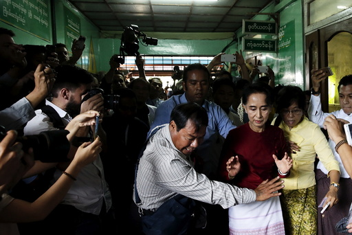 Myanmar's National League for Democracy party leader Aung San Suu Kyi reacts as some cameramen fell to the floor before casting her ballot during the general election in Yangon