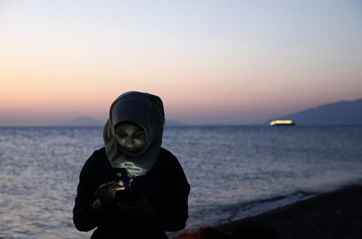 A Syrian refugee sends text messages to relatives moments after arriving at a beach on the Greek island of Kos