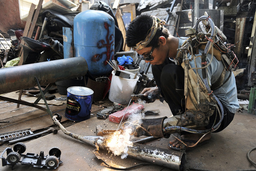 Mechanic I Wayan Sumardana, also known as Tawan, uses what he calls a robotic arm he said he made himself, while welding a client's motorbike part at his garage in the village of Nyuh Tebel
