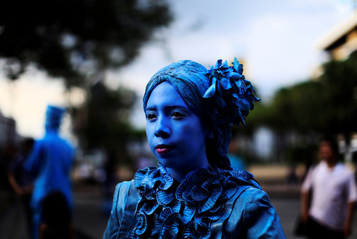 A contestant performs during a living statue contest in downtown San Salvador