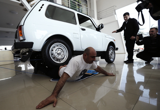 Yajian reacts as a four wheel car drives over him during his attempt to break a Guinness record in Tbilisi