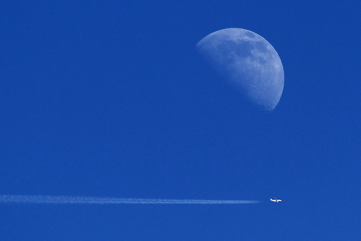 An aircraft flies past the moon over Ardales,near Malaga, southern Spain