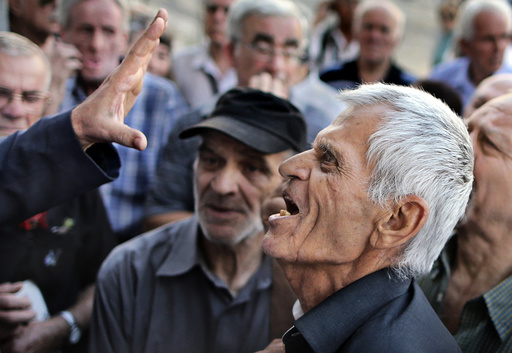 A pensioner argues with an official as he tries to enter a National Bank branch to receive part of his pension in Athens