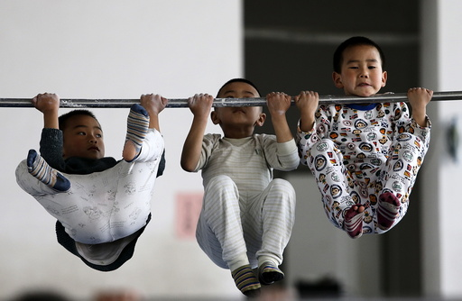 Young gymnasts practice pull-up on a bar at a gymnasium of a sports school in Jiaxing