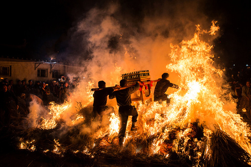 Men carrying a shrine jump over a bon fire, which means a wish for good luck during a traditional Chinese lunar new year celebration in Jieyang