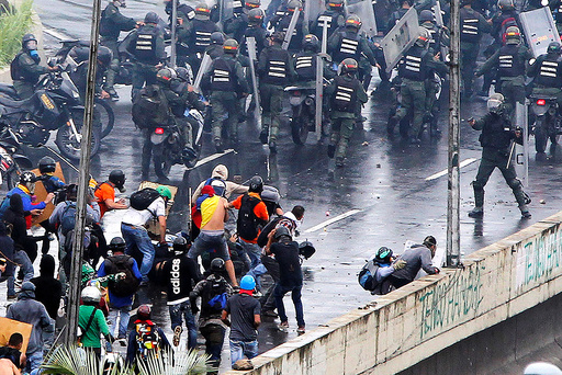 A member of the riot security forces points what appears to be a pistol towards a crowd of demonstrators during a rally against Venezuelaâä™s President Nicolas Maduroâä™s government in Caracas,