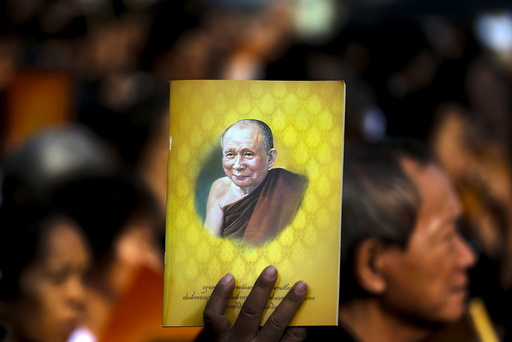 Man holds up a picture of Thailand's Supreme Patriarch, Somdet Phra Nyanasamvara Somdet Phra Sangharaja, as he takes part in a cremation ceremony in Bangkok