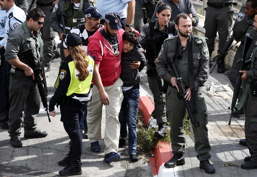 Israeli police lead away a Palestinian minor in Pisgat Zeev