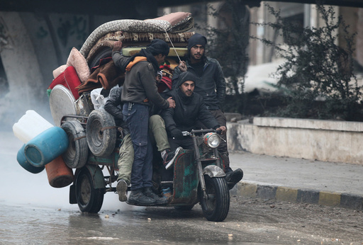 Men ride a tricycle as they flee deeper into the remaining rebel-held areas of Aleppo