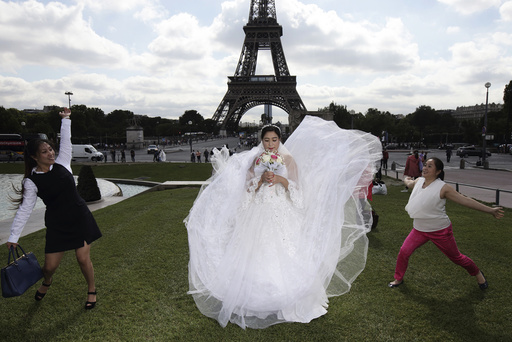 A Chinese future bride has her friends playing with her dress during a pre-wedding photoshoot in front of the Eiffel tower in Paris