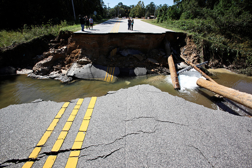Residents inspect a washed-out section of collapsed road after Hurricane Matthew hit the state, in Fayetteville, North Carolina