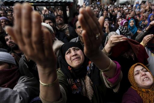 Kashmiri Muslims raise their arms upon seeing a relic of Sheikh Abdul Qadir Jeelani, a Sufi saint, being displayed at his shrine in Srinagar