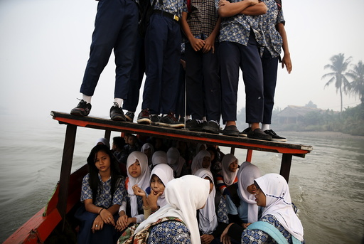Students stand on the roof of a wooden boat as haze blankets the Musi River while they travel to school in Palembang